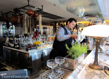 Herbs grow at the bar, meats and cheese hang behind